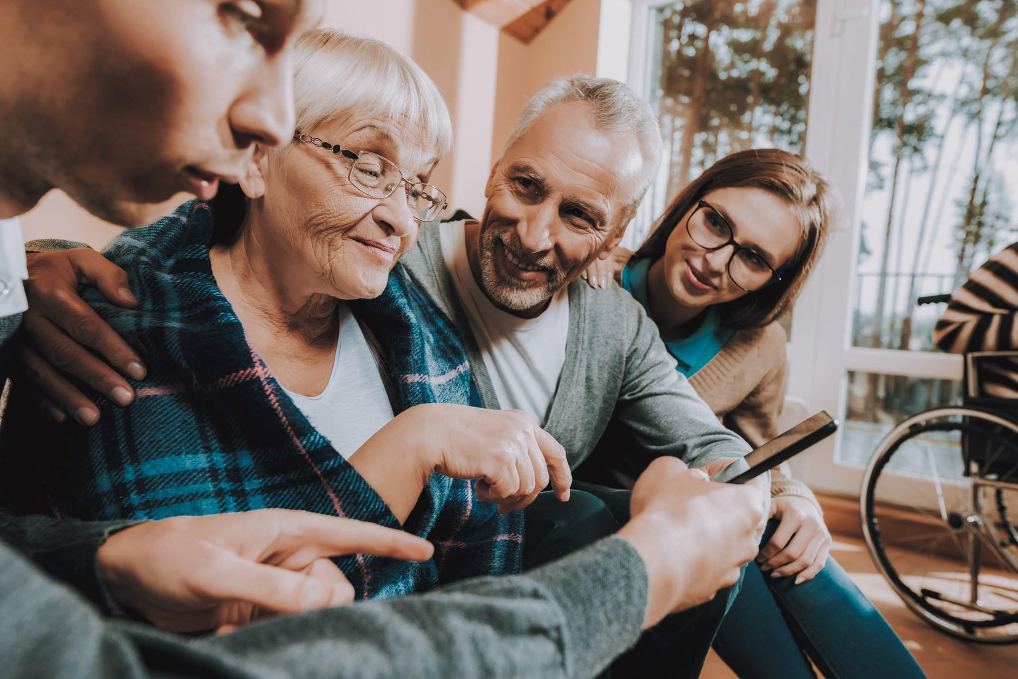 elderly people sitting around smart phone